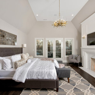 Example of a large transitional master dark wood floor and brown floor bedroom design in Chicago with a standard fireplace, a stone fireplace and beige walls