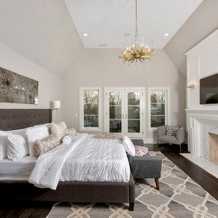 Свежая идея для дизайна: большая хозяйская спальня в стиле современная классика с темным паркетным полом, стандартным камином, фасадом камина из камня, коричневым полом и бежевыми стенами - отличное фото интерьера