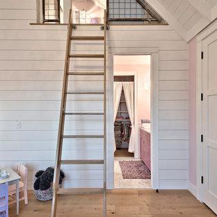 Modelo de dormitorio tipo loft, campestre, de tamaño medio, con paredes rosas y suelo de madera clara