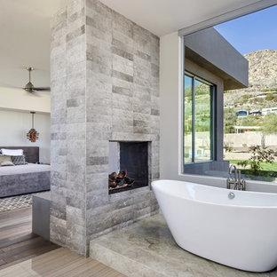 Diseño de dormitorio principal, moderno, grande, con paredes blancas, suelo de madera oscura, chimenea de doble cara y marco de chimenea de piedra