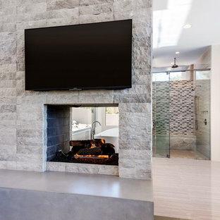 Esempio di una grande camera matrimoniale moderna con pareti bianche, pavimento in legno massello medio, camino bifacciale e cornice del camino in pietra