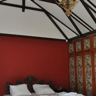 Ejemplo de dormitorio principal, grande, con paredes rojas, suelo de madera oscura, estufa de leña, marco de chimenea de madera y suelo marrón