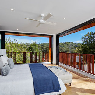 Contemporary master bedroom in Sydney with white walls, medium hardwood floors and brown floor.