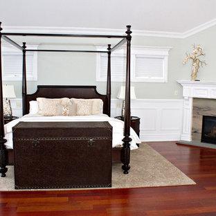 ニューヨークの大きいトラディショナルスタイルのおしゃれな主寝室 (グレーの壁、濃色無垢フローリング、コーナー設置型暖炉、石材の暖炉まわり、赤い床)