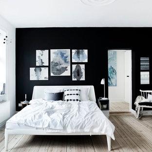 Imagen de dormitorio principal, escandinavo, de tamaño medio, con paredes negras y suelo de madera clara
