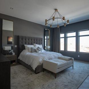 Modelo de dormitorio principal, contemporáneo, de tamaño medio, sin chimenea, con paredes grises, suelo de baldosas de porcelana y suelo gris