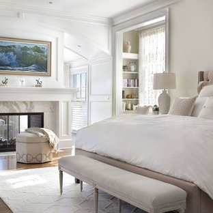 Photo of a traditional master bedroom in New York with beige walls, dark hardwood floors, a two-sided fireplace, a stone fireplace surround and brown floor.