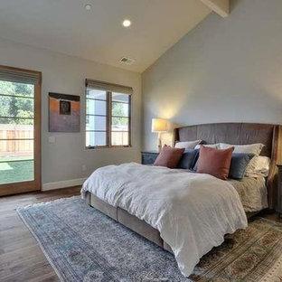 Foto de dormitorio principal, rústico, extra grande, con paredes beige, suelo de madera en tonos medios, chimenea tradicional y marco de chimenea de yeso