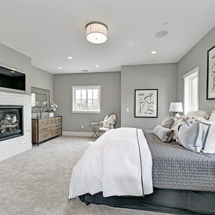 Example of a large transitional master carpeted bedroom design in San Francisco with gray walls, a standard fireplace and a stone fireplace