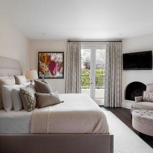 サンタバーバラの中サイズの地中海スタイルのおしゃれな主寝室 (白い壁、濃色無垢フローリング、コーナー設置型暖炉、漆喰の暖炉まわり、茶色い床) のレイアウト