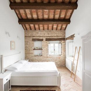 Idée de décoration pour une chambre parentale champêtre de taille moyenne avec un mur blanc et un sol en brique.