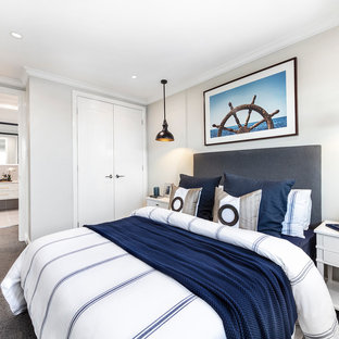Design ideas for a beach style master bedroom in Brisbane with grey walls, carpet, no fireplace and grey floor.
