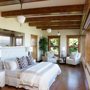 Ejemplo de dormitorio principal, exótico, de tamaño medio, sin chimenea, con paredes blancas, suelo de madera oscura y suelo marrón
