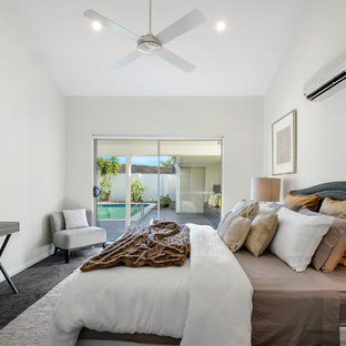 Design ideas for a beach style master bedroom in Brisbane with white walls, carpet and black floor.