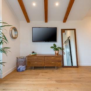 ロサンゼルスの広いミッドセンチュリースタイルのおしゃれな客用寝室 (黄色い壁、無垢フローリング、ベージュの床) のインテリア