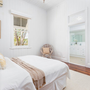 Inspiration for a scandinavian master bedroom in Brisbane with white walls, medium hardwood floors and brown floor.