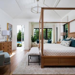 Cette image montre une grande chambre parentale marine avec un mur blanc, un sol en bois brun et un sol marron.