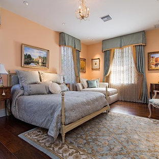 Example of a large french country master dark wood floor bedroom design in Miami with orange walls