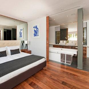 Foto di una camera da letto minimalista con pareti bianche e pavimento in legno massello medio
