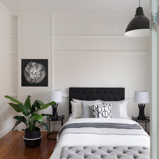 Design ideas for a beach style bedroom in Brisbane with white walls, medium hardwood floors and brown floor.