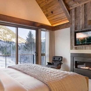 На фото: большая хозяйская спальня в стиле рустика с бежевыми стенами, ковровым покрытием, горизонтальным камином, фасадом камина из металла и бежевым полом