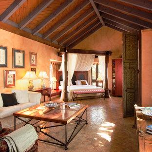 Ispirazione per un'ampia camera matrimoniale mediterranea con pavimento in terracotta e pareti arancioni