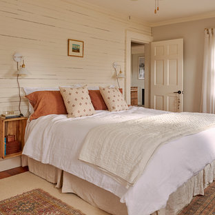 Country bedroom in New York with beige walls and panelled walls.