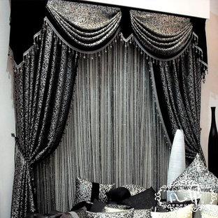 Imagen de dormitorio principal, moderno, grande, con paredes negras, suelo de ladrillo, chimeneas suspendidas, marco de chimenea de yeso y suelo negro