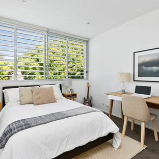 Design ideas for a beach style guest bedroom in Sydney with white walls, carpet and brown floor.