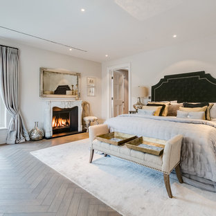 Large traditional master bedroom in London with white walls, light hardwood flooring, a standard fireplace and beige floors.