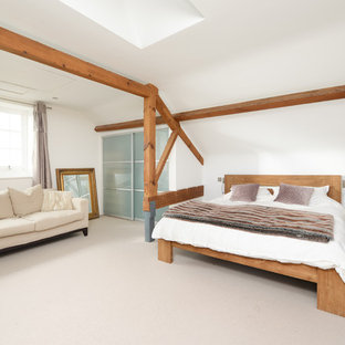 Photo of a farmhouse bedroom in Kent with white walls, carpet and grey floors.