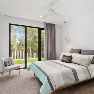 Contemporary bedroom in Melbourne with white walls, carpet and beige floor.