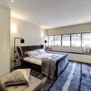 Large contemporary master bedroom in London with grey walls, dark hardwood flooring and brown floors.