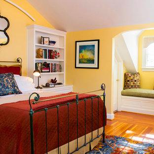 Idée de décoration pour une chambre d'amis craftsman de taille moyenne avec un mur jaune, un sol en bois brun et aucune cheminée.