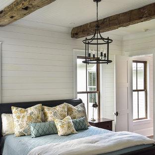 Пример оригинального дизайна: хозяйская спальня в стиле кантри с белыми стенами, темным паркетным полом, стандартным камином, фасадом камина из дерева и коричневым полом