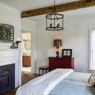Ejemplo de dormitorio principal, de estilo de casa de campo, con paredes blancas, suelo de madera oscura, chimenea tradicional, marco de chimenea de madera y suelo marrón