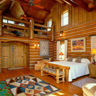 Ejemplo de dormitorio tipo loft, rústico, de tamaño medio, con suelo de madera en tonos medios y paredes marrones