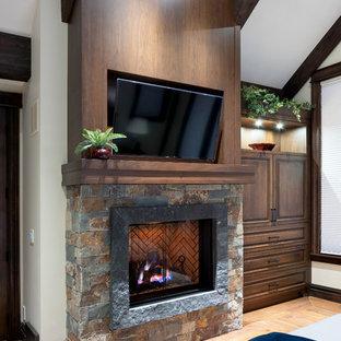 Idee per una camera matrimoniale rustica con pareti beige, pavimento in legno massello medio, camino classico, cornice del camino in pietra e pavimento nero