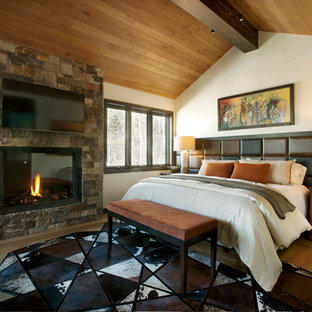 Example of a mountain style master medium tone wood floor and brown floor bedroom design in Denver with white walls, a standard fireplace and a stone fireplace