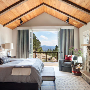 Inspiration for a large rustic master bedroom remodel in Denver with white walls and a standard fireplace