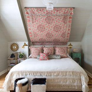 Foto di una camera da letto boho chic con pareti grigie e pavimento in legno massello medio