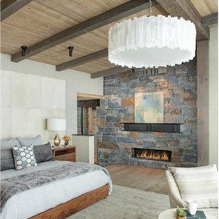 Diseño de dormitorio principal, rural, grande, con paredes grises, suelo de madera en tonos medios, chimenea lineal, marco de chimenea de piedra y suelo marrón