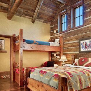 Ejemplo de habitación de invitados rústica, de tamaño medio, con paredes amarillas y suelo de madera en tonos medios