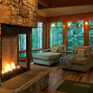 Inspiration for a transitional master bedroom in Denver with beige walls, medium hardwood floors, a two-sided fireplace and a stone fireplace surround.