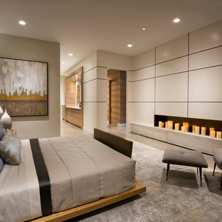 Photo of a large contemporary master bedroom in Phoenix with beige walls, limestone flooring, a ribbon fireplace and beige floors.
