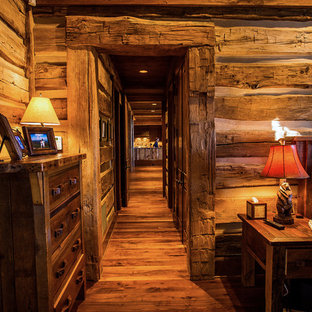 Mid-sized mountain style guest dark wood floor bedroom photo in Other with brown walls