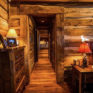 На фото: с высоким бюджетом гостевые спальни среднего размера в стиле рустика с коричневыми стенами и темным паркетным полом