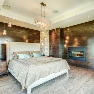 Idéer för att renovera ett stort funkis huvudsovrum, med bruna väggar, ljust trägolv, en dubbelsidig öppen spis och en spiselkrans i trä
