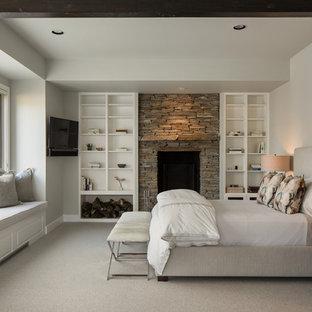 Klassisk inredning av ett mellanstort huvudsovrum, med vita väggar, heltäckningsmatta, en standard öppen spis, en spiselkrans i sten och vitt golv