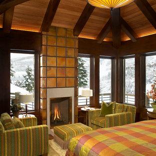 На фото: большая хозяйская спальня в стиле рустика с коричневыми стенами, стандартным камином и фасадом камина из плитки с